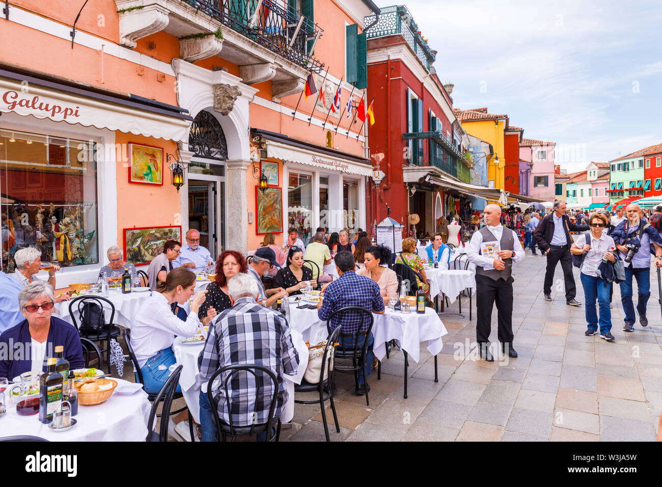 Tourists eating al fresco outside at tables in the street in the busy, bustling centre of Burano, a small island in Venice Lagoon, Venice, Italy - Stock Image