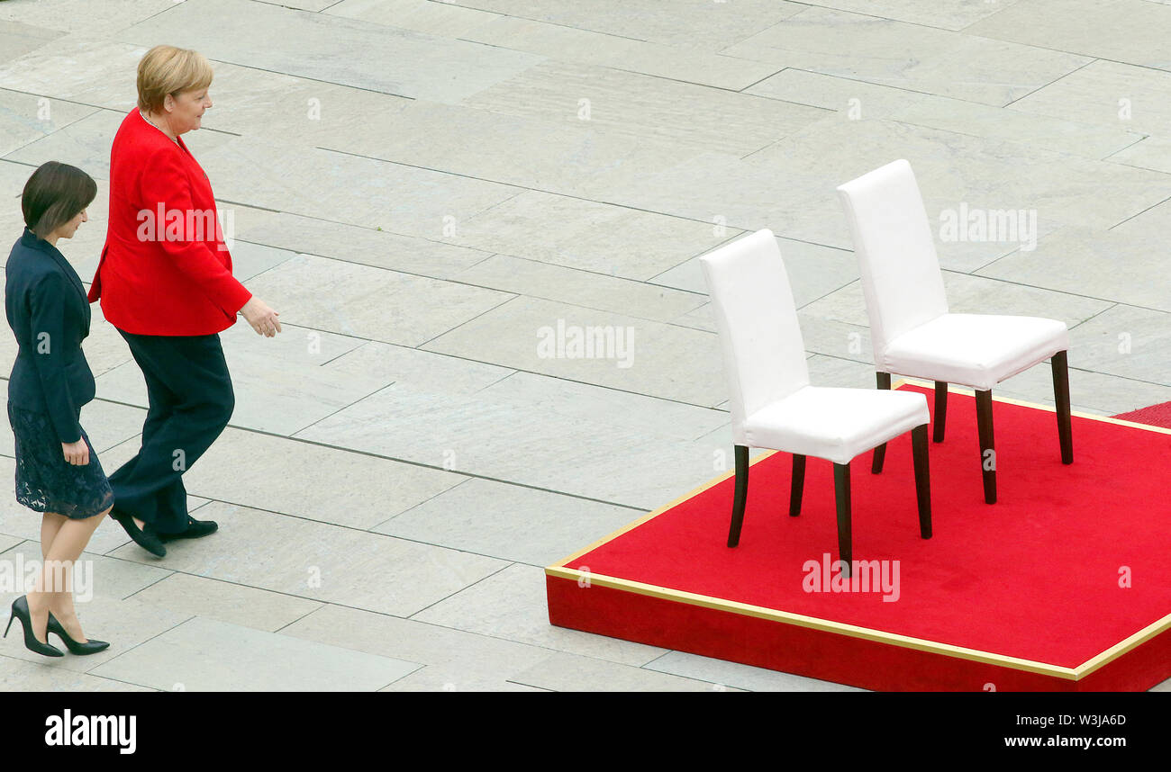 Berlin, Germany. 16th July, 2019. Federal Chancellor Angela Merkel (CDU, r) receives Moldovan Prime Minister Maia Sandu in the Federal Chancellery with military honours. After several tremors during public appearances such as this, Merkel performed the ceremony for the first time last week, partly sitting down. Credit: Wolfgang Kumm/dpa/Alamy Live News - Stock Image