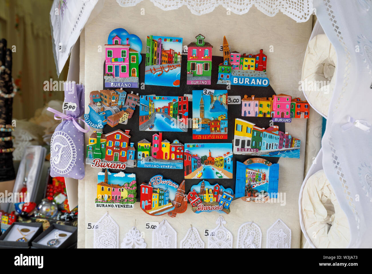 Display of brightly coloured fridge magnets with views of Burano and its colourful houses in a town centre souvenir shop, Burano, Venice Lagoon, Italy - Stock Image