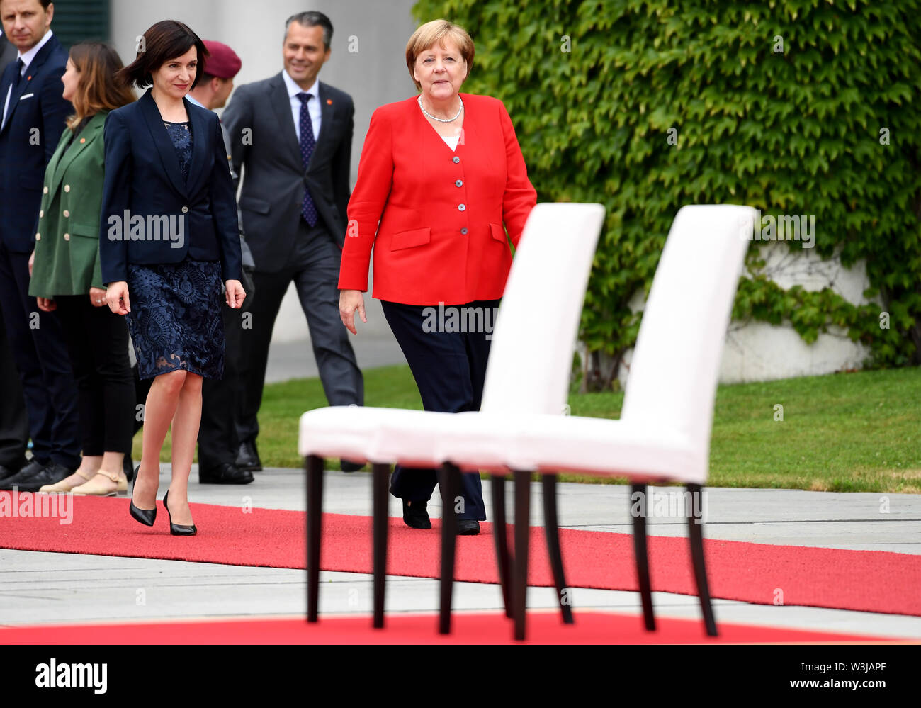 Berlin, Germany. 16th July, 2019. Federal Chancellor Angela Merkel (CDU, r) receives Moldovan Prime Minister Maia Sandu in the Federal Chancellery with military honours. After several tremors during public appearances such as this, Merkel performed the ceremony for the first time last week, partly sitting down. Credit: Britta Pedersen/dpa-Zentralbild/dpa/Alamy Live News - Stock Image