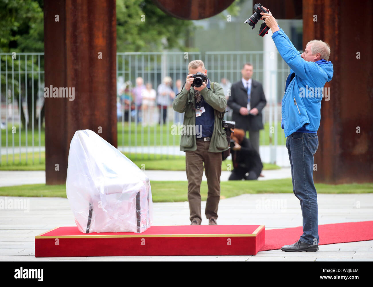 Berlin, Germany. 16th July, 2019. Journalists in the Federal Chancellery's Court of Honour document chairs wrapped in rain gear on which Chancellor Merkel and the Prime Minister of Molda, Sandu, will watch the national anthems play. After several tremors during public appearances such as this, Merkel performed the ceremony for the first time last week, partly sitting down. Credit: Wolfgang Kumm/dpa/Alamy Live News - Stock Image
