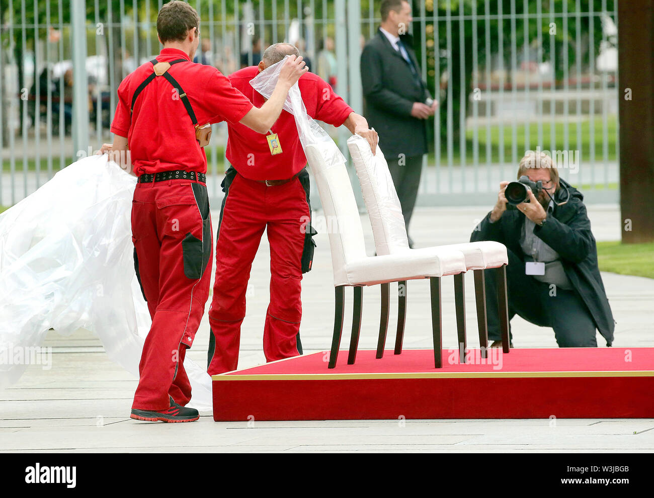 Berlin, Germany. 16th July, 2019. Employees of the Chancellery remove a rain shield from chairs in the Federal Chancellery's courtyard of honour on which Chancellor Merkel and the Prime Minister of Molda, Sandu, will watch the national anthems being played. After several tremors during public appearances such as this, Merkel performed the ceremony for the first time last week, partly sitting down. Credit: Wolfgang Kumm/dpa/Alamy Live News - Stock Image