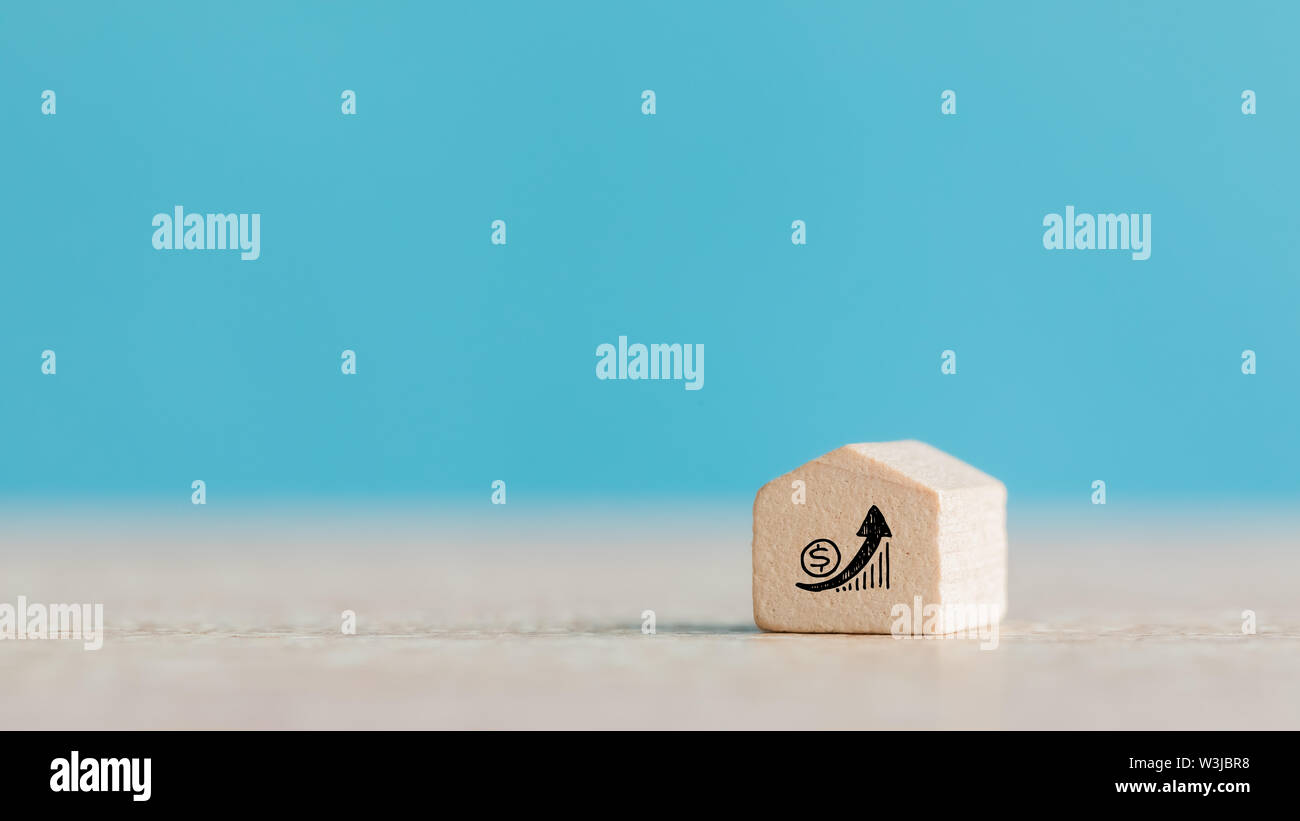Real Estate and Housing Property Market Concept using Wooden House Model on Blue Background Stock Photo