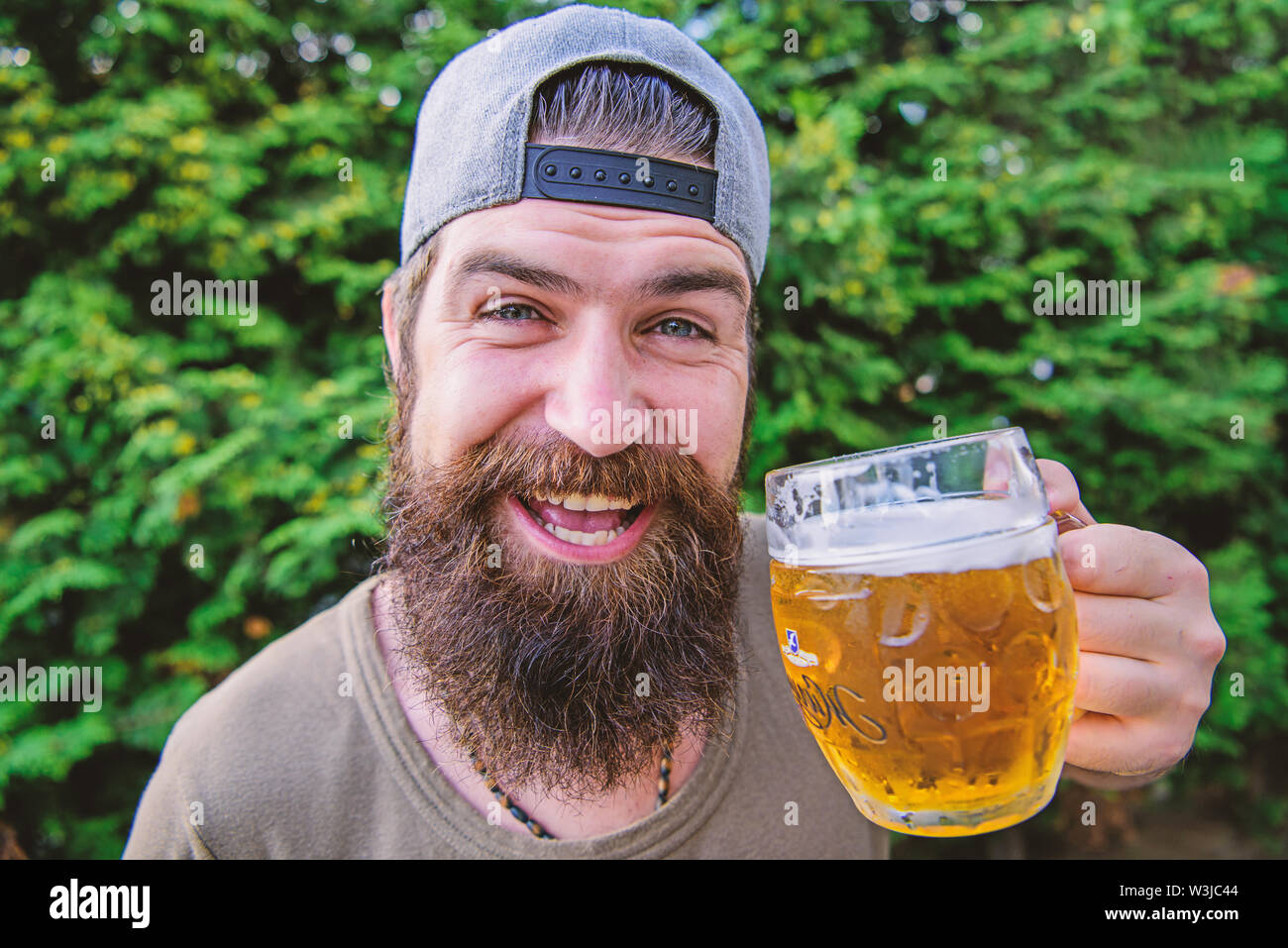 I need a cold one. Happy hipster holding beer mug. Bearded man happy smiling with beer on nature. Happy drinker. Beer is proof that God wants us to be happy. - Stock Image