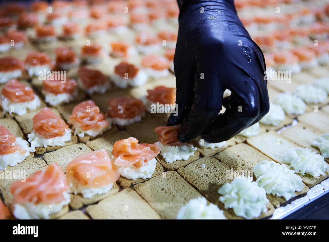 Chef making Norwegian Smoked Salmon Canapes with Cream Cheese - Stock Image