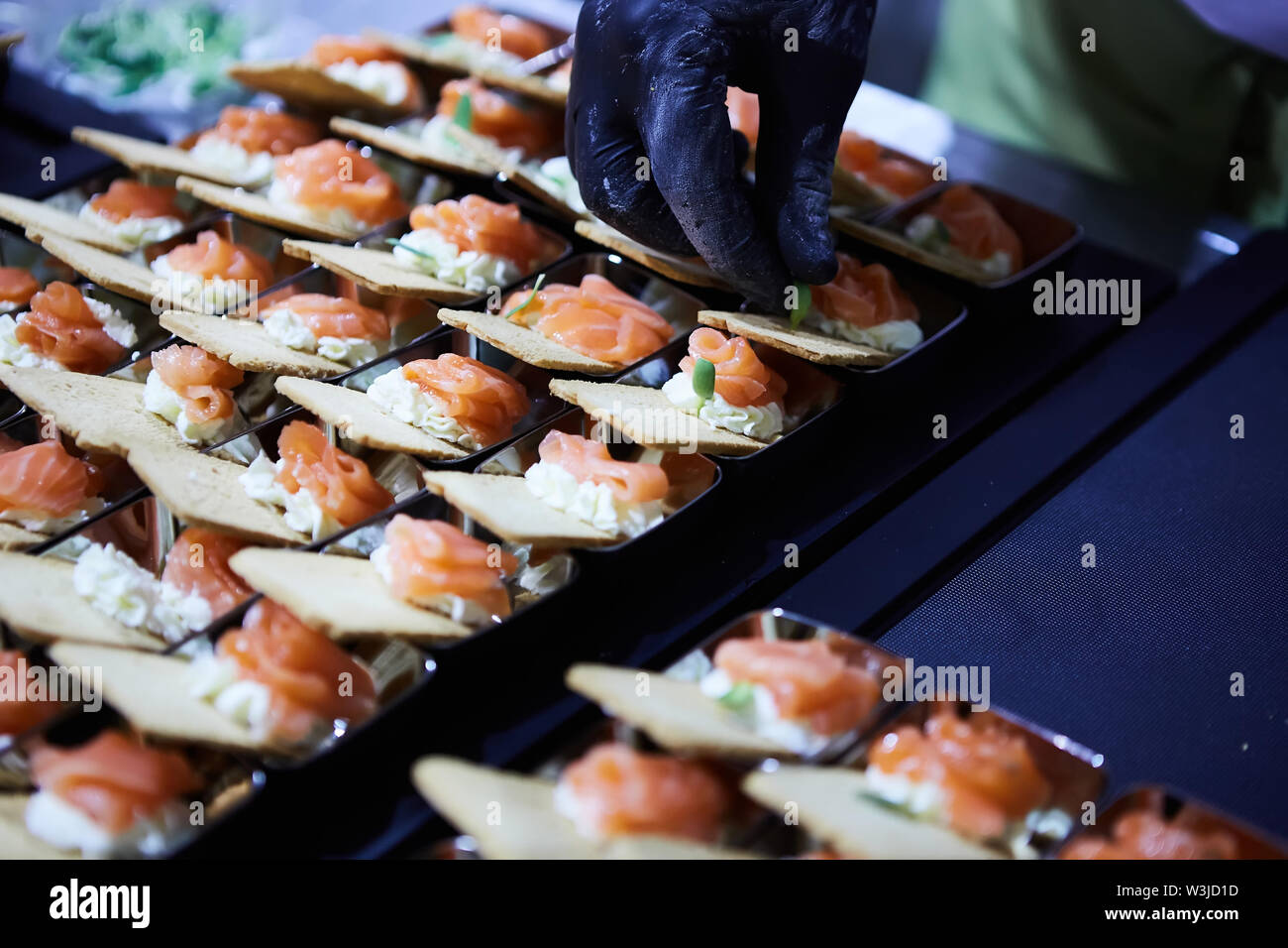 Chef making Norwegian Smoked Salmon Canapes with Cream Cheese Stock Photo