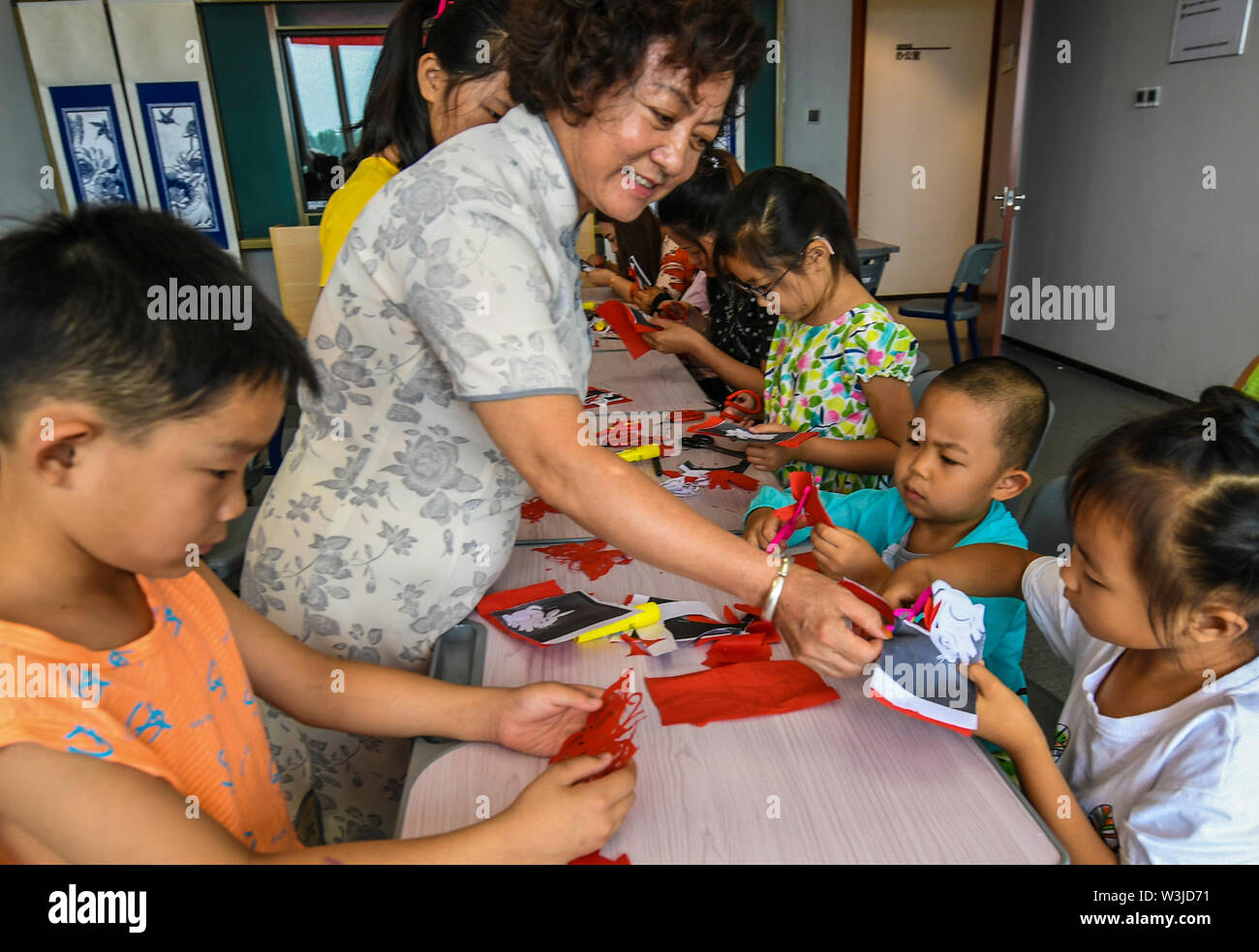 (190716) -- XIANGHE, July 16, 2019 (Xinhua) -- Folk artists instruct children to do paper cutting in Xianghe County, north China's Hebei Province, July 16, 2019. The activity was organized by the local government to help children appreciate the traditional culture during their summer vacation. (Xinhua/Li Xiaoguo) - Stock Image