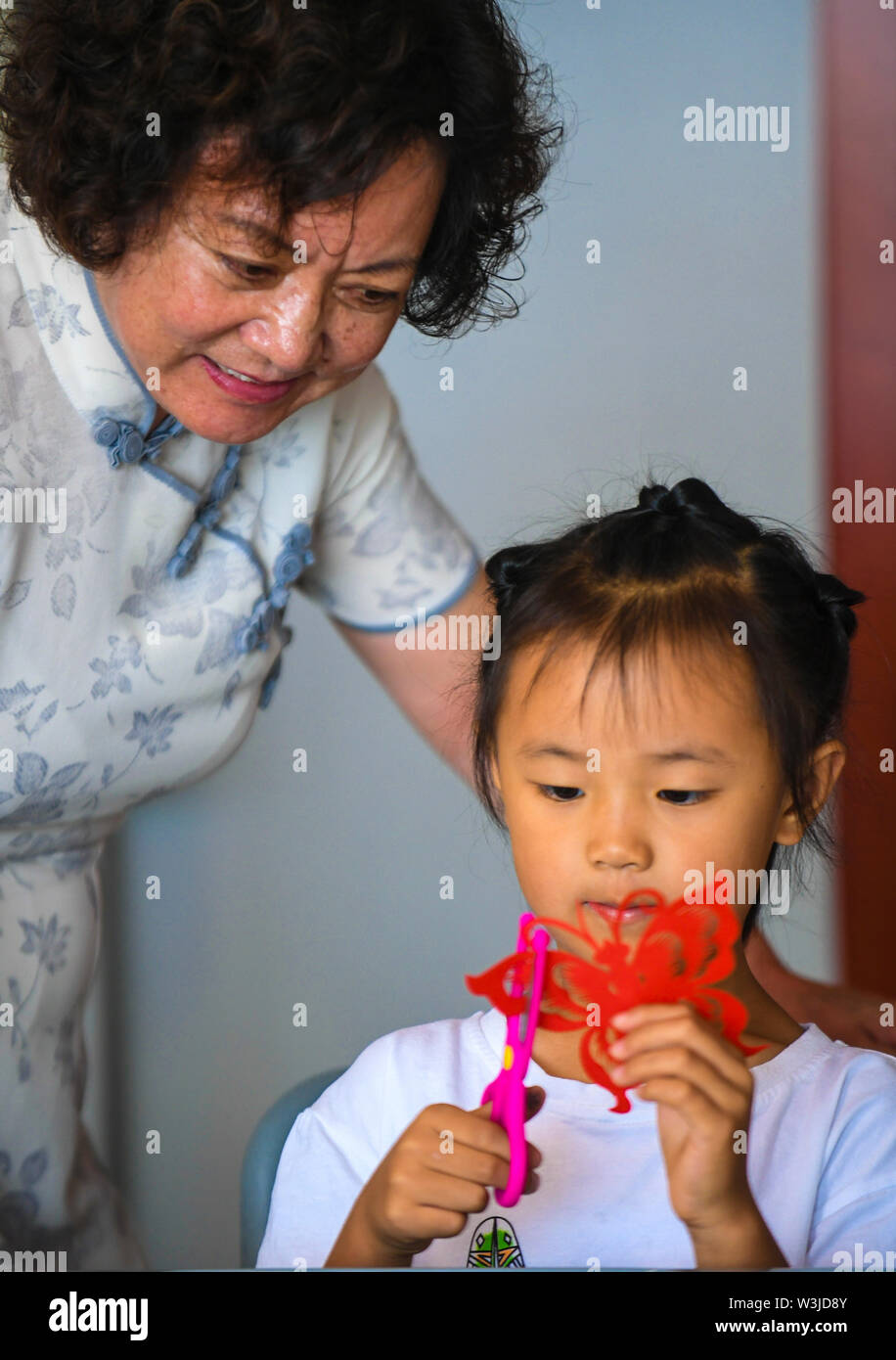 Xianghe, China's Hebei Province. 16th July, 2019. A folk artist instructs a girl to do paper cutting in Xianghe County, north China's Hebei Province, July 16, 2019. The activity was organized by the local government to help children appreciate the traditional culture during their summer vacation. Credit: Li Xiaoguo/Xinhua/Alamy Live News - Stock Image