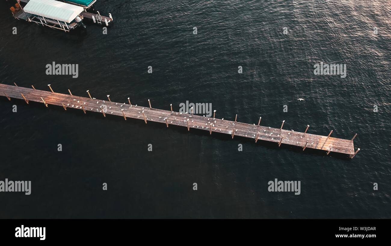 An aerial shot of a long wooden pier and amazing texture of the water - Stock Image