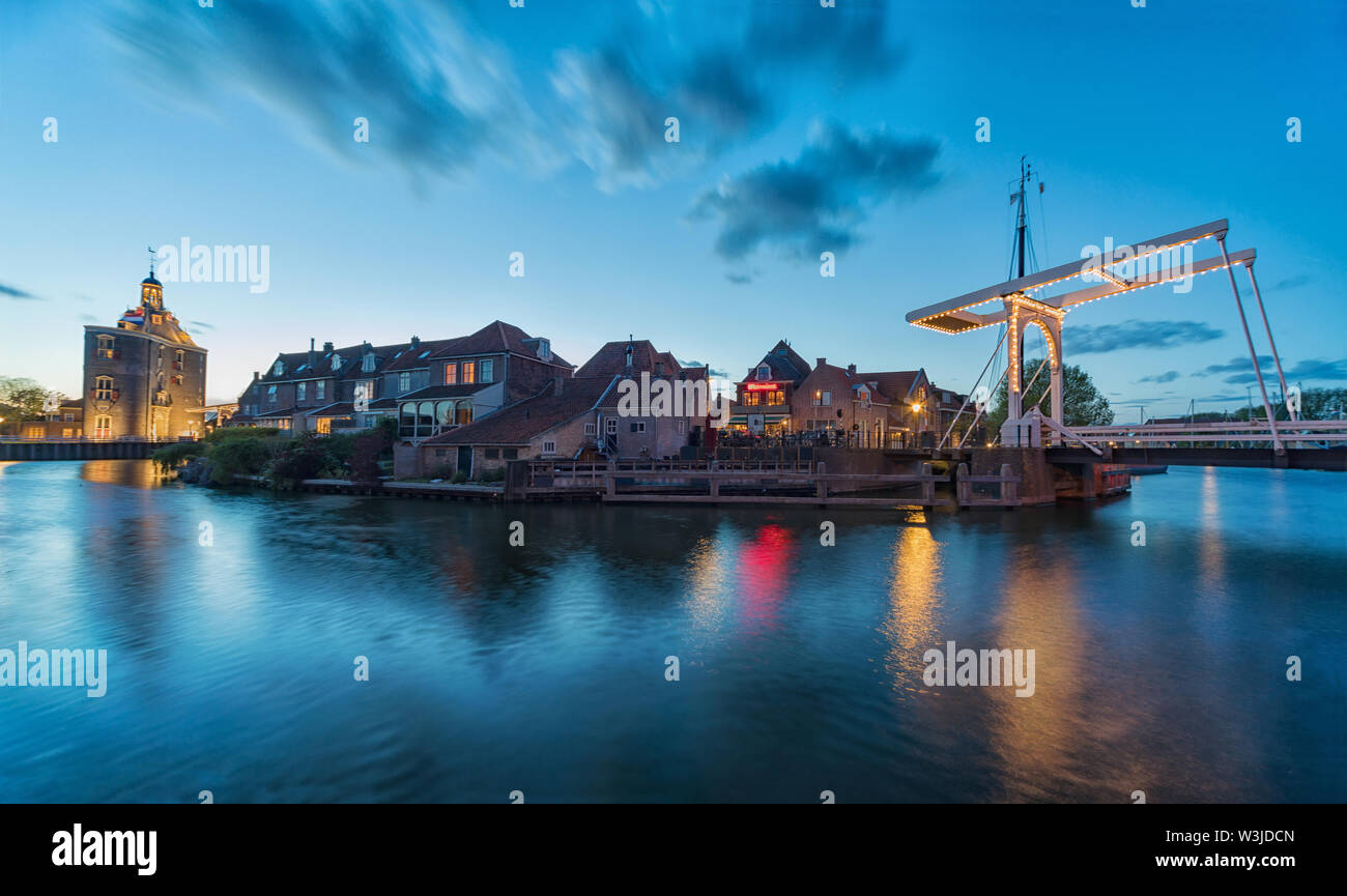 The center of Enkhuizen in the Netherlands with the old city gate - Drommedaris in the background, during the blue hour - dusk. - Stock Image