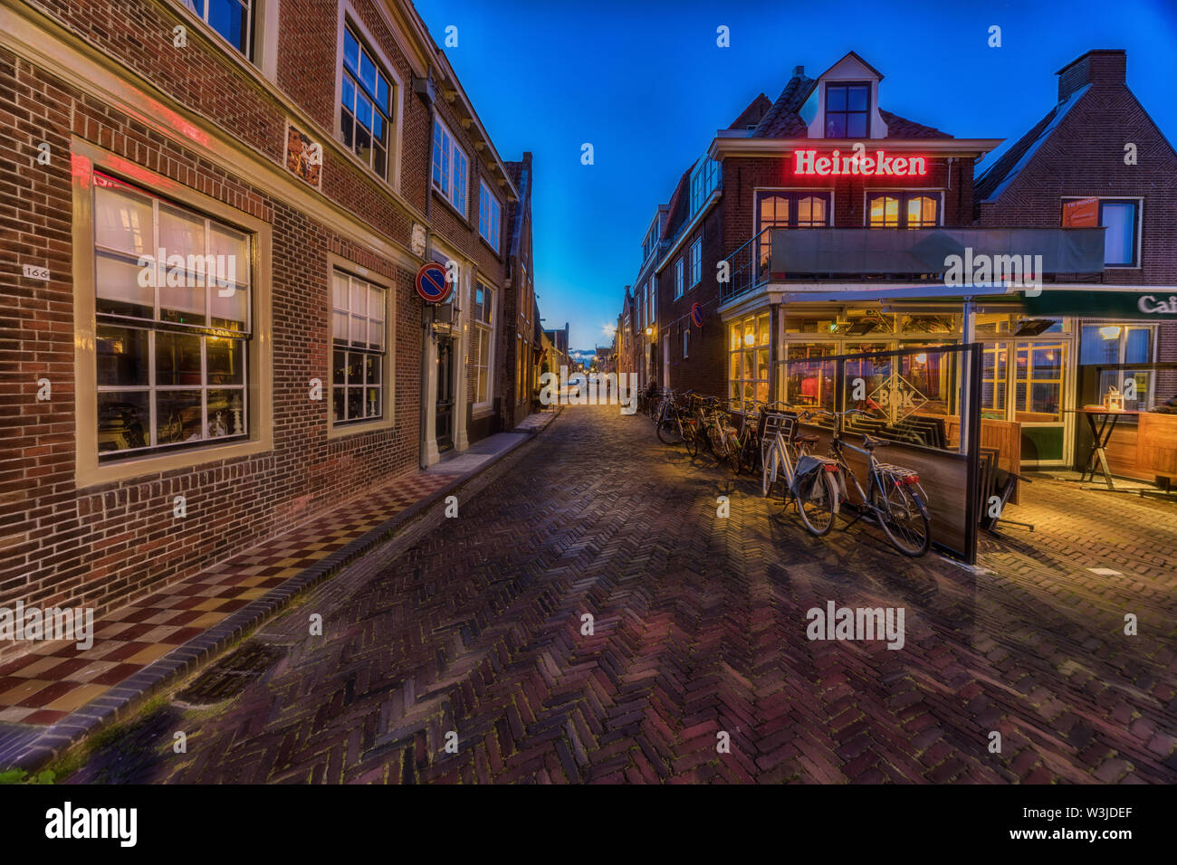 Enkhuizen, The Netherlands - May 04, 2019: Old street in Enkhuizen at the IJsselmeer in the Netherlands during dusk. - Stock Image