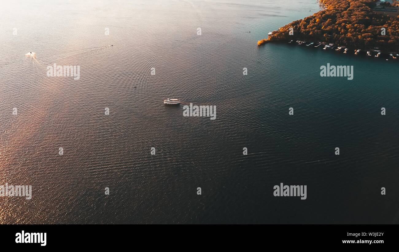 An aerial shot of a large cruise ship sailing in the sea with greenery on the side - Stock Image