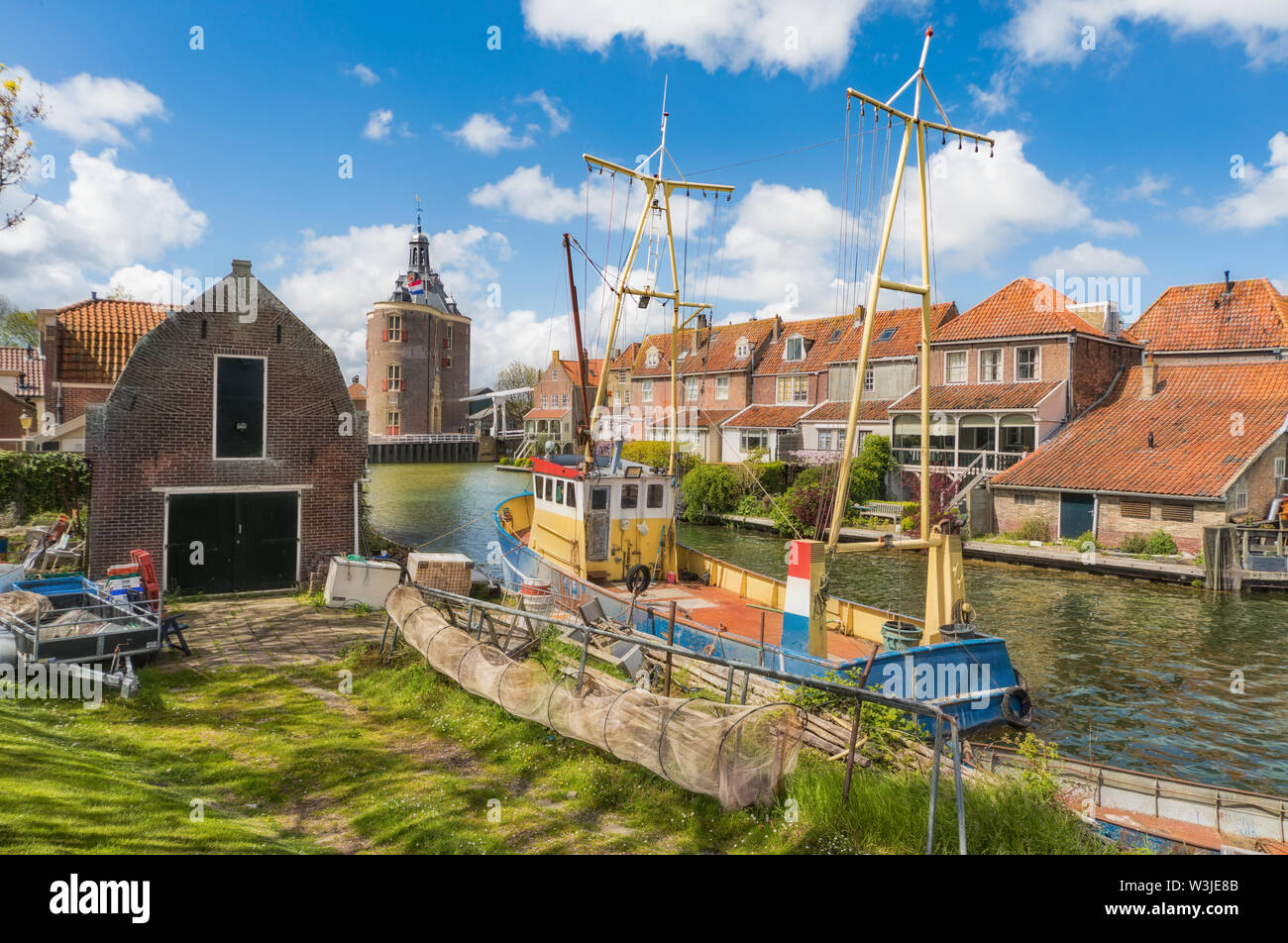 Fishing boat in Enkhuizen in the Netherlands with the historic city gate (Drommedaris) in the background. - Stock Image