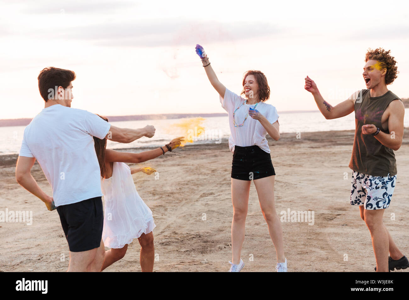 Group of a cheerful young friends having fun at the beach with colorful holi paint - Stock Image