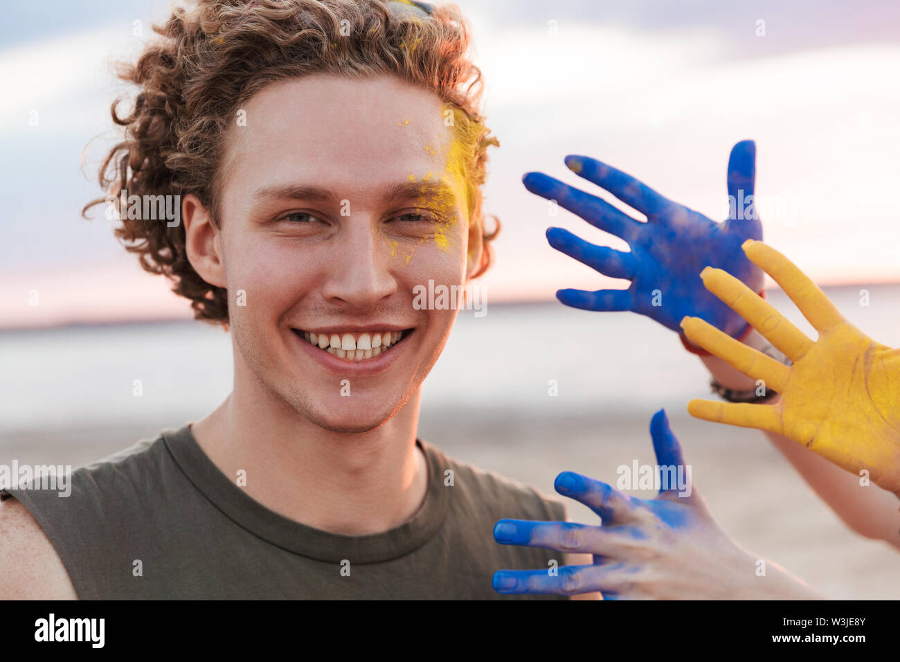 Cheerful young man standing at the beach, celebrating with colorful holi paint - Stock Image