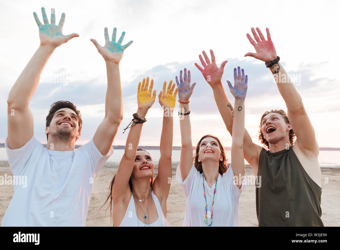 Group of a cheerful young friends having fun at the beach with colorful holi paint, showing hands - Stock Image