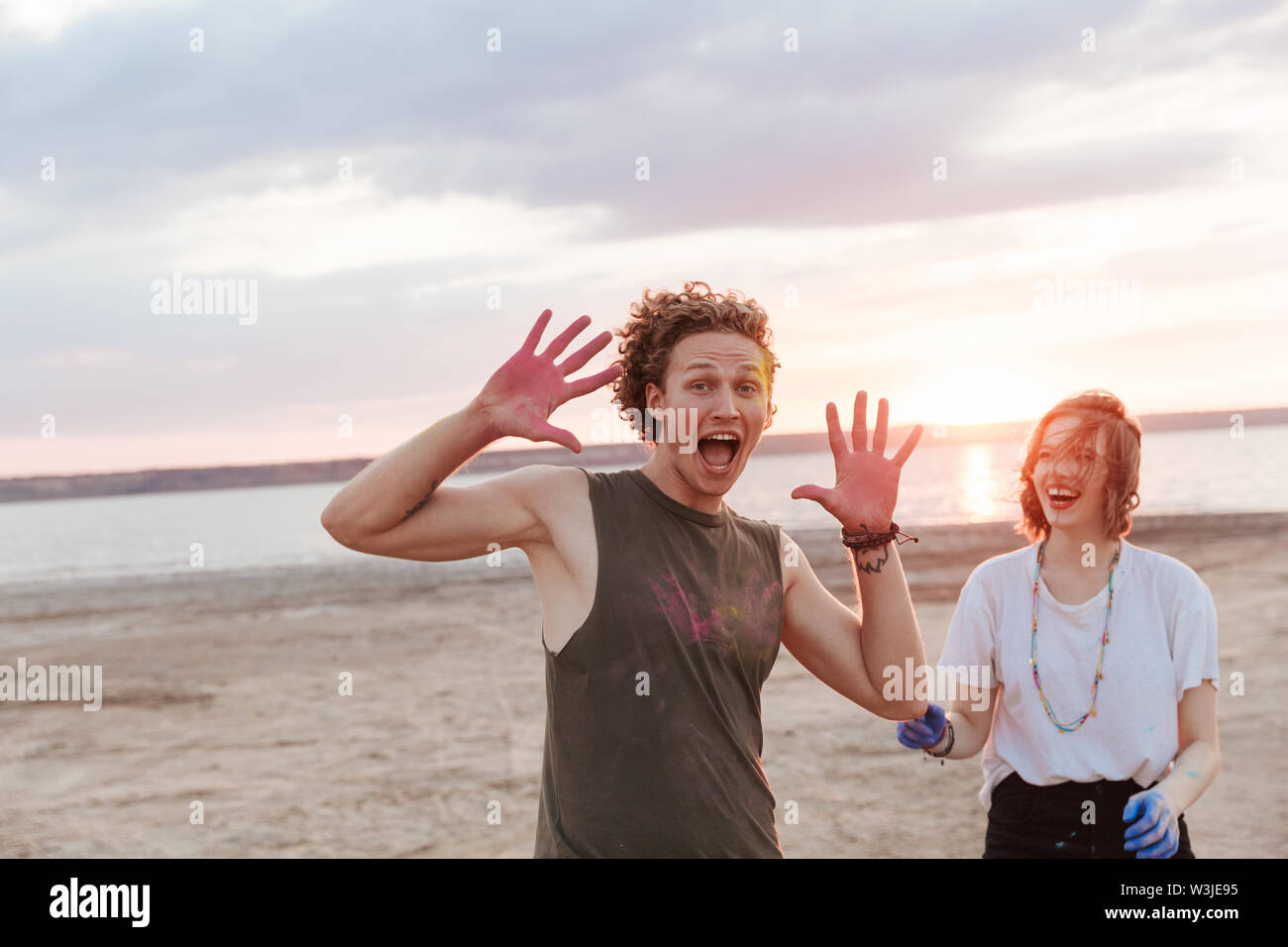Two cheerful young friends having fun at the beach with colorful holi paint - Stock Image