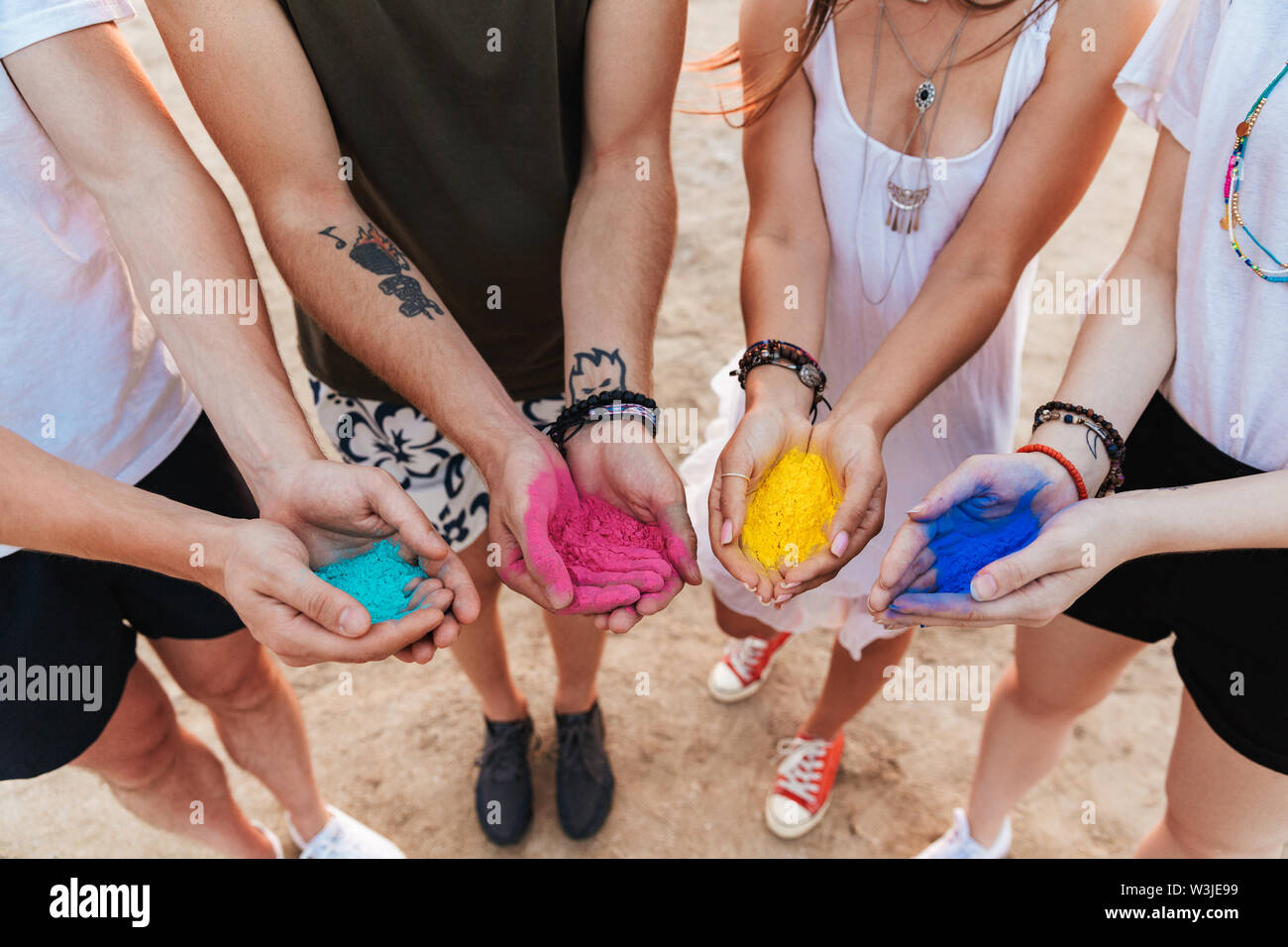 Group of a cheerful young friends having fun at the beach, showing hands with colorful holi paint - Stock Image