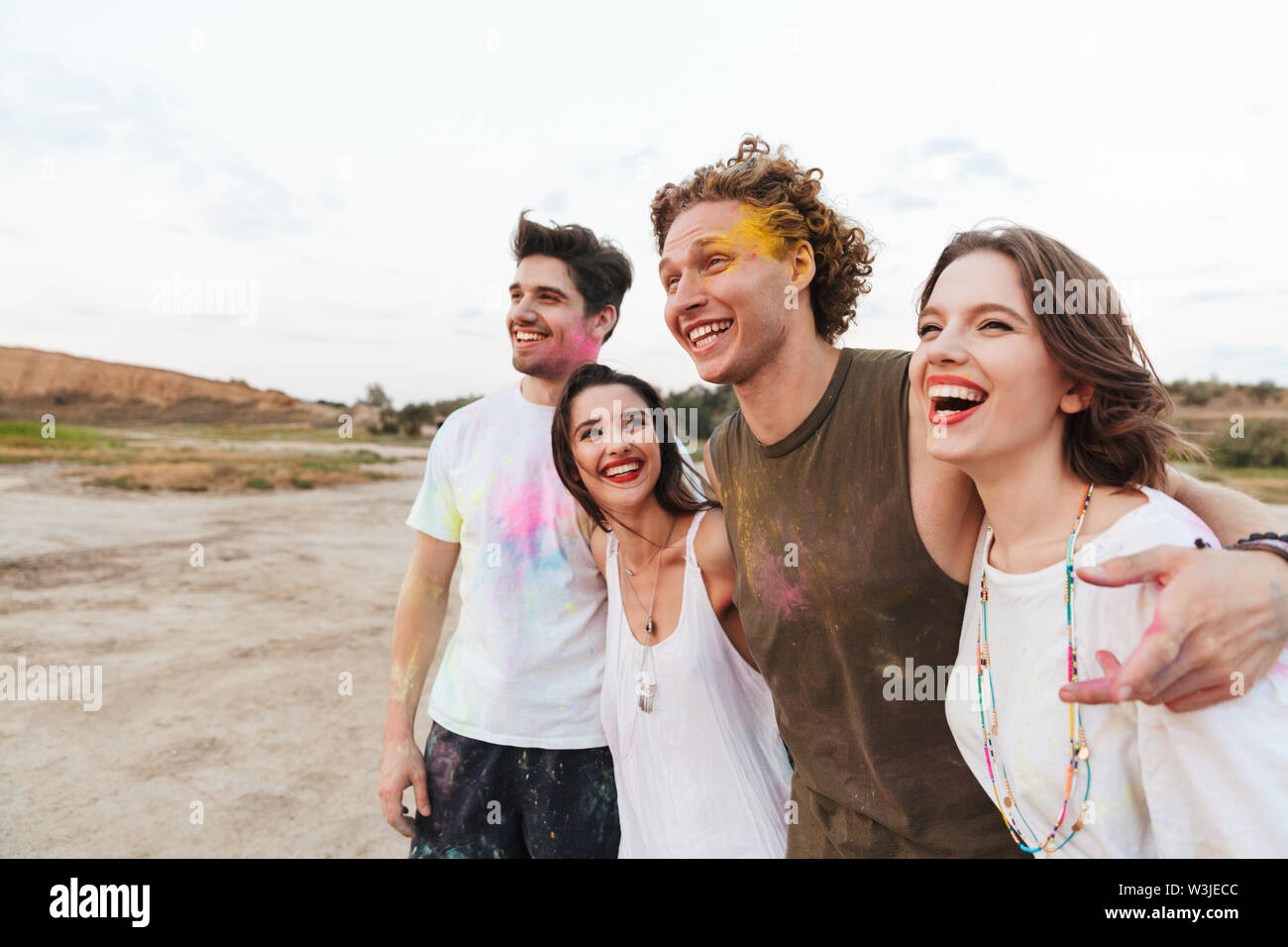 Group of a cheerful young friends having fun at the beach with colorful holi paint Stock Photo