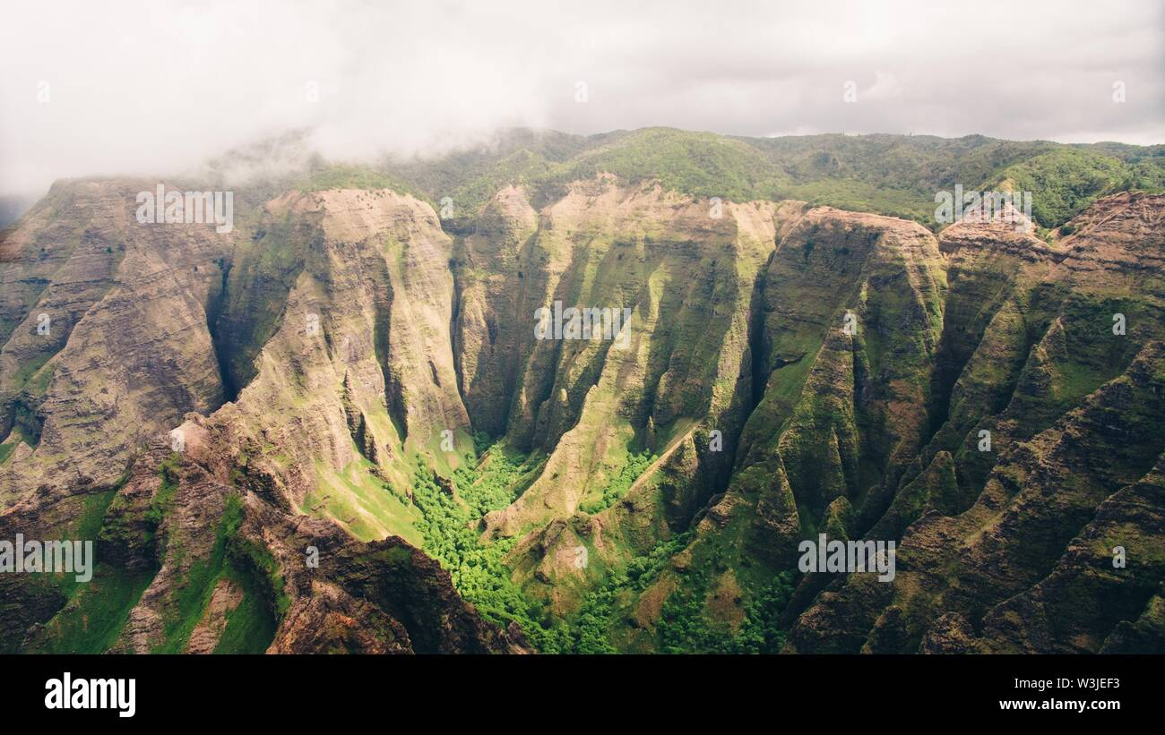 A high angle shot of  island of Kauai beautiful mountains in a fog with greenery - Stock Image