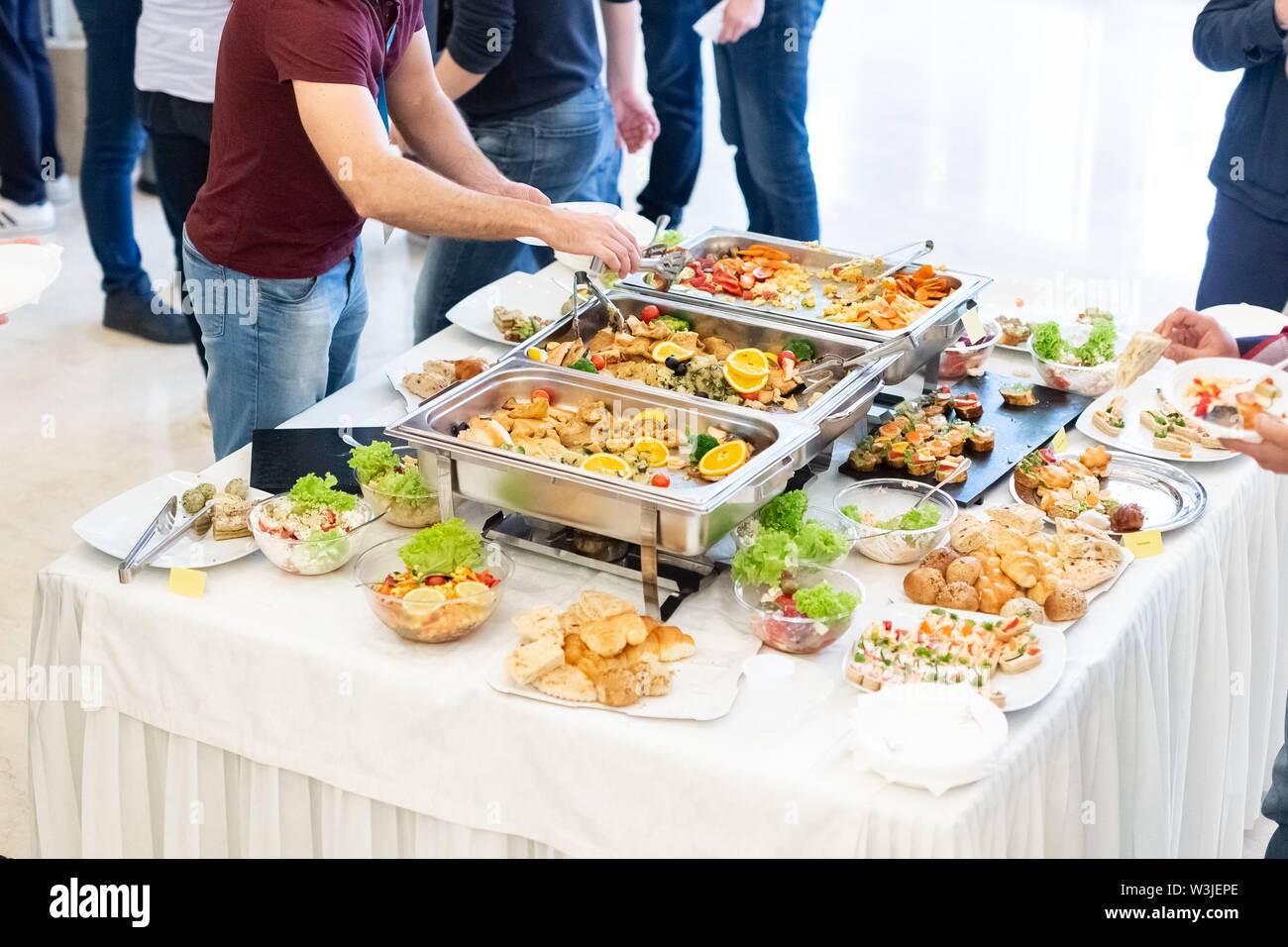 Close up of people serving themselves in buffet of restaurant. - Stock Image
