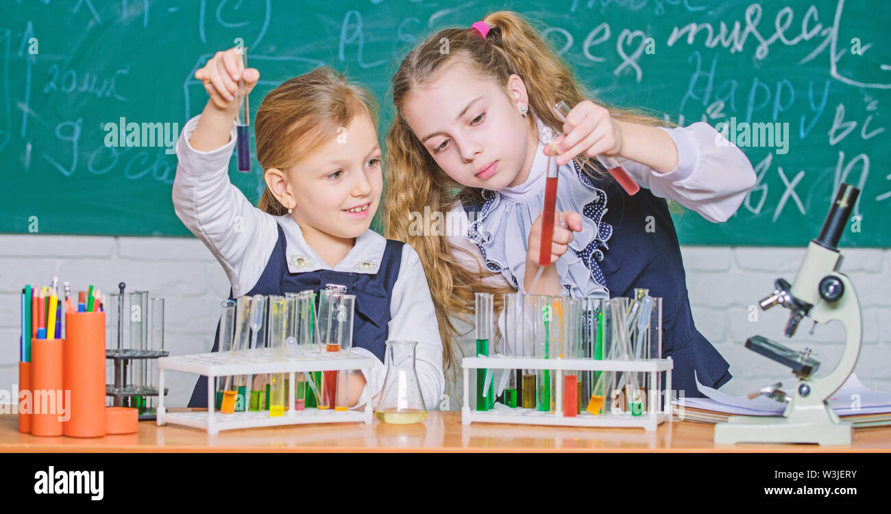 Chemistry is about reaction. Smart school children performing chemistry test in lab. Small schoolgirls learning chemistry during school time. Little pupils holding test tubes in chemistry laboratory. Stock Photo