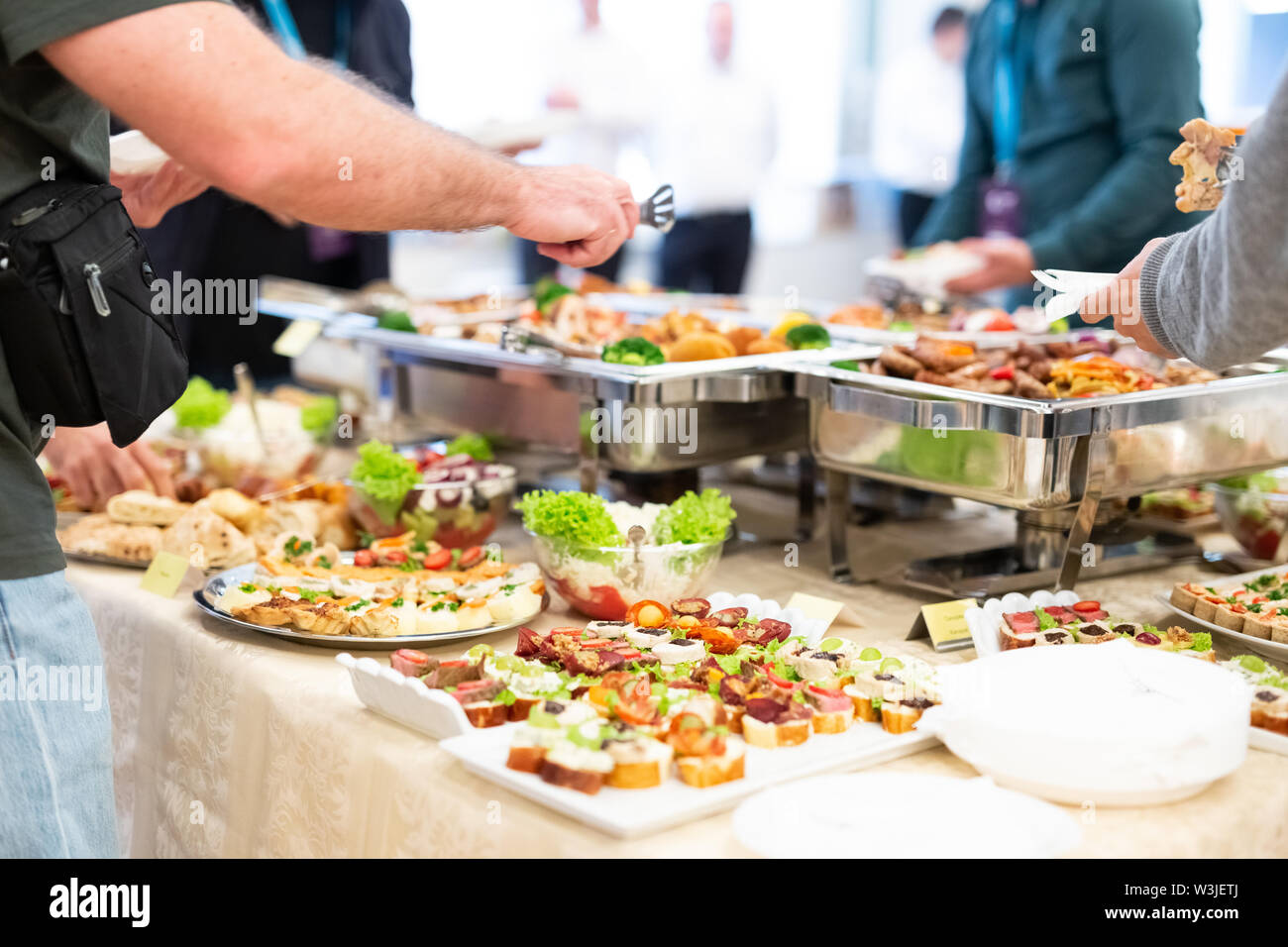 Close up of people serving themselves with canapes in buffet of restaurant. - Stock Image