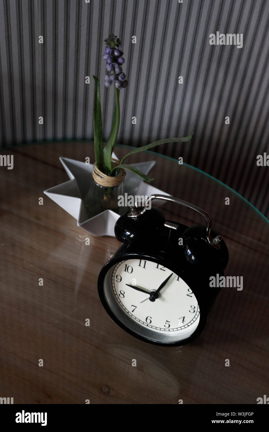 Alarm clock by bed - Stock Image