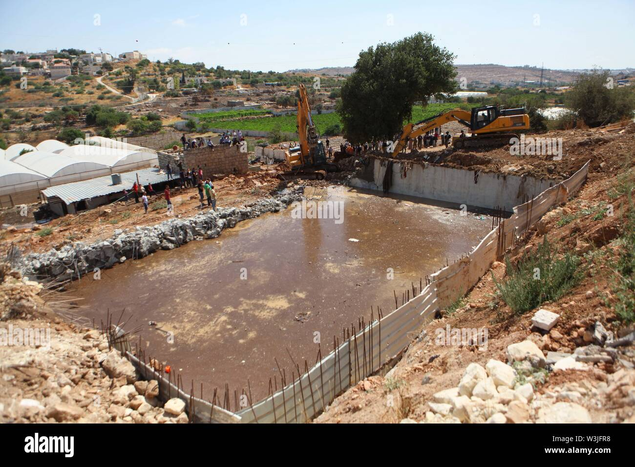 Hebron. 16th July, 2019. Israeli bulldozers demolish a water facility in 'Area C' of the West Bank city of Hebron, July 16, 2019. The Israeli army demolished water wells and other facilities used by Palestinians in the area for lacking construction license. Credit: Mamoun Wazwaz/Xinhua/Alamy Live News - Stock Image