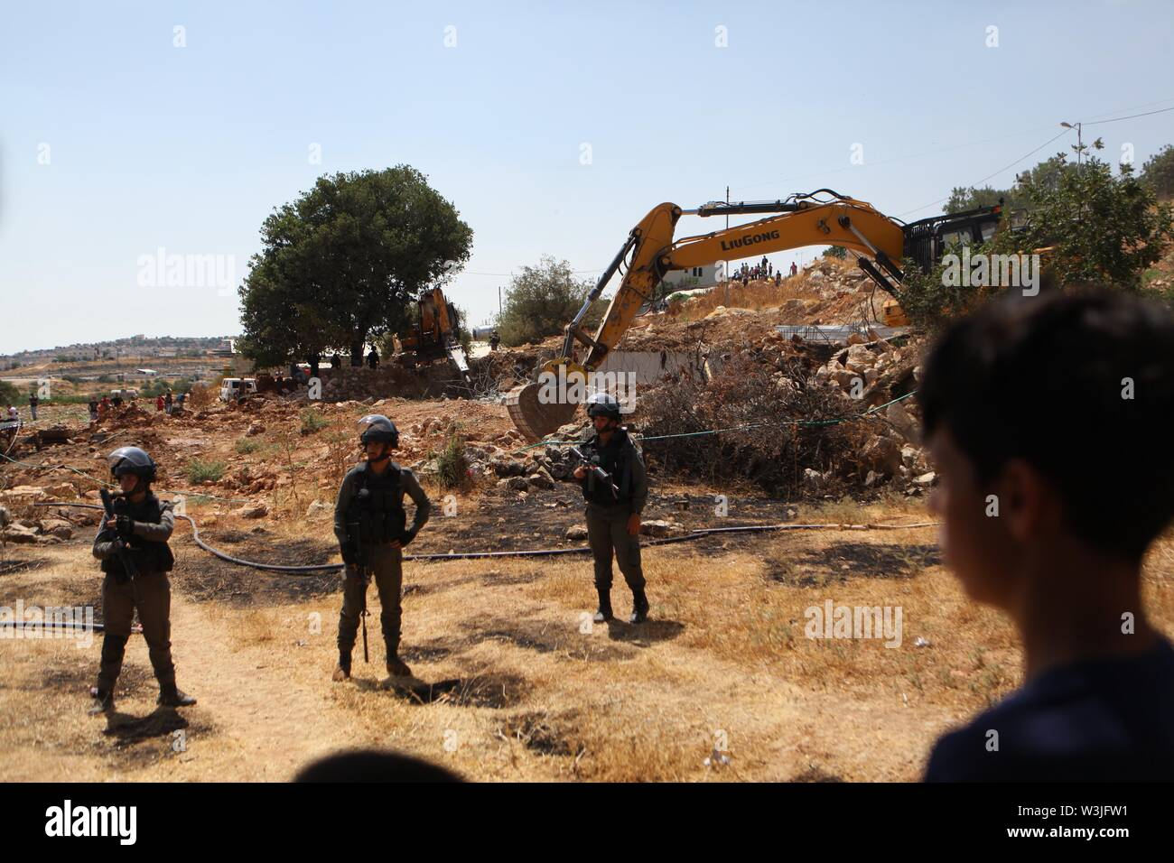 Hebron. 16th July, 2019. Israeli bulldozers demolish water wells in 'Area C' of the West Bank city of Hebron, July 16, 2019. The Israeli army demolished water wells and other facilities used by Palestinians in the area for lacking construction license. Credit: Mamoun Wazwaz/Xinhua/Alamy Live News - Stock Image