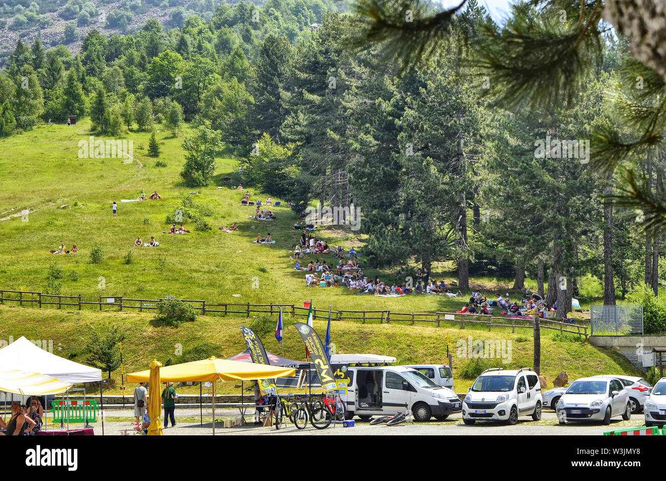 Colle del Lys, Piedmont, Italy. July 2019. People looking for refreshment take advantage of the slope of the mountain with a large green lawn to picni - Stock Image