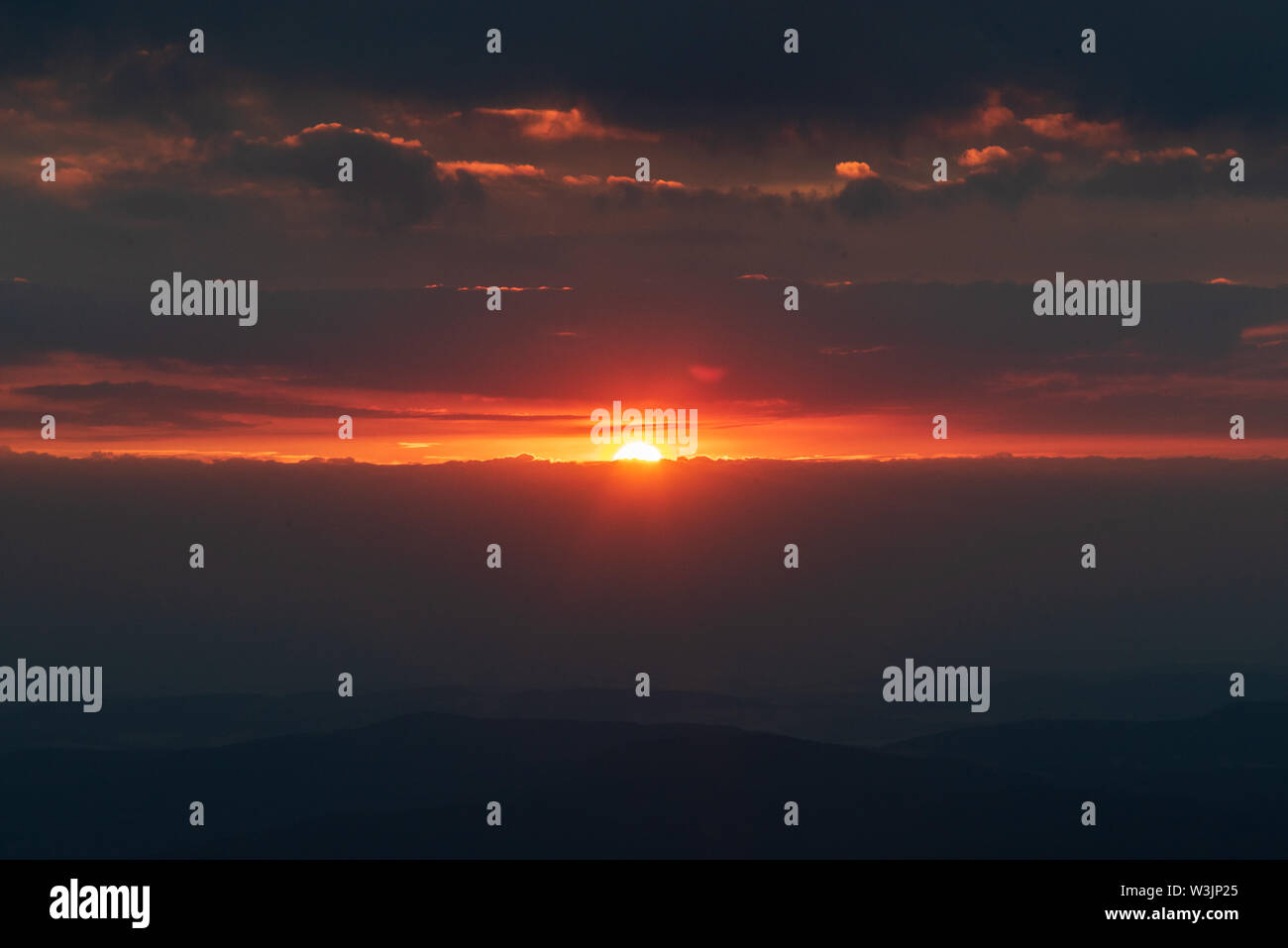 sunrise with clouds, hills silhouette and colorful sky from Snezka hill in Krkonose mountains on czech-polish borders - Stock Image
