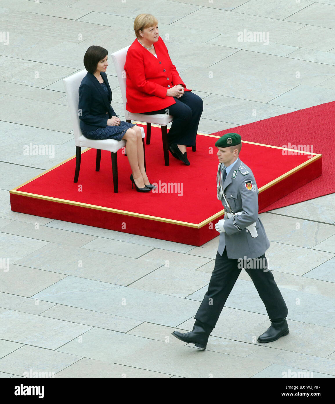 Berlin, Germany. 16th July, 2019. Federal Chancellor Angela Merkel (CDU, r) receives Moldovan Prime Minister Maia Sandu in the Federal Chancellery with military honours and follows the national anthems playing while sitting with her. After several tremors during public appearances such as this, Merkel performed the ceremony for the first time last week, partly sitting down. Credit: Wolfgang Kumm/dpa/Alamy Live News - Stock Image