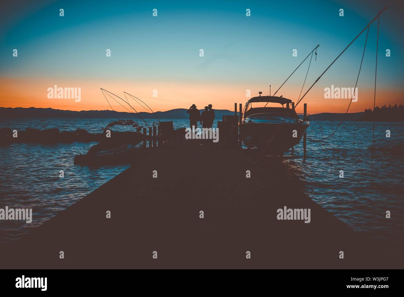 A people standing on a dock near the boats at sunset in Lake Tahoe, NV. - Stock Image