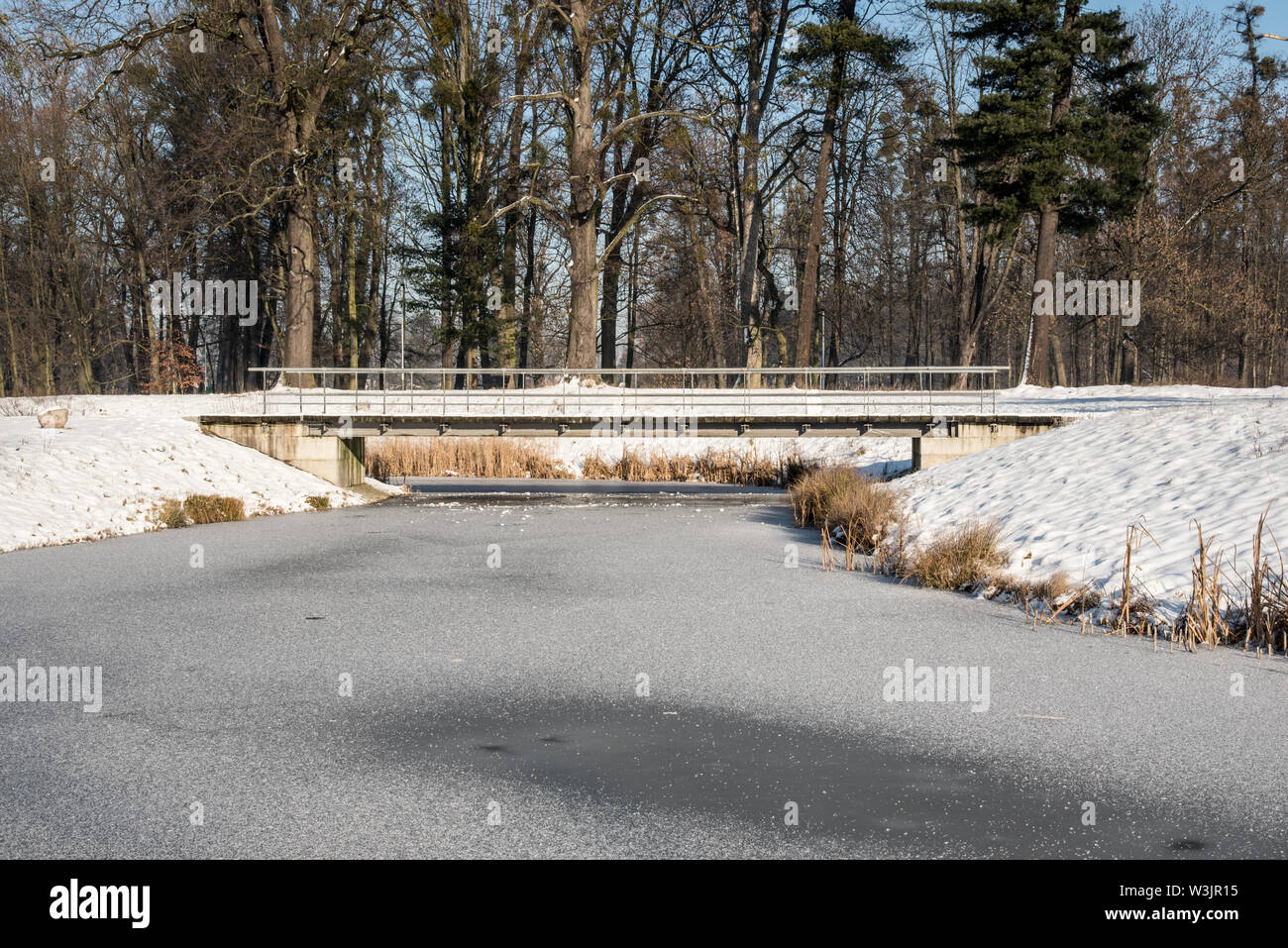 fozen Mlynka creek with bridge above and trees on the background on Park Bozeny Nemcove public park in Karvina city in Czech republic during beuatiful Stock Photo