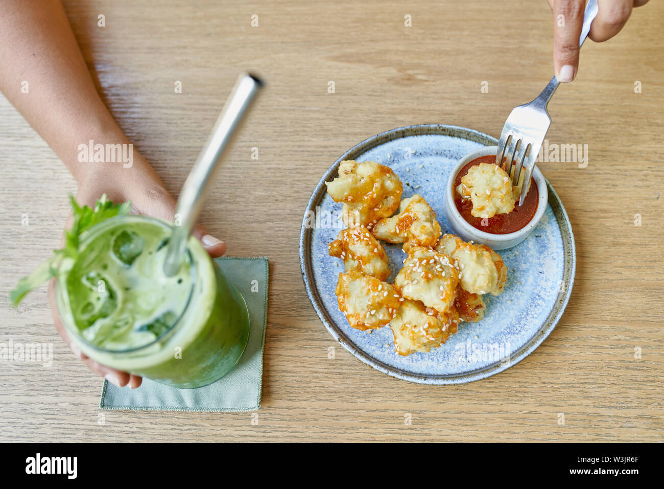Overhead shot of tasty fine vegetarian plant-based cuisine on artisanal ceramic plate including fried cauliflower and sauce, with a green smoothie and - Stock Image