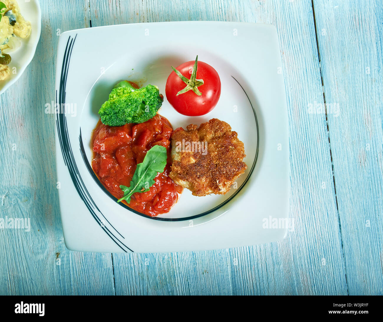 Fried cod with curry sauce and vegetables , close up - Stock Image