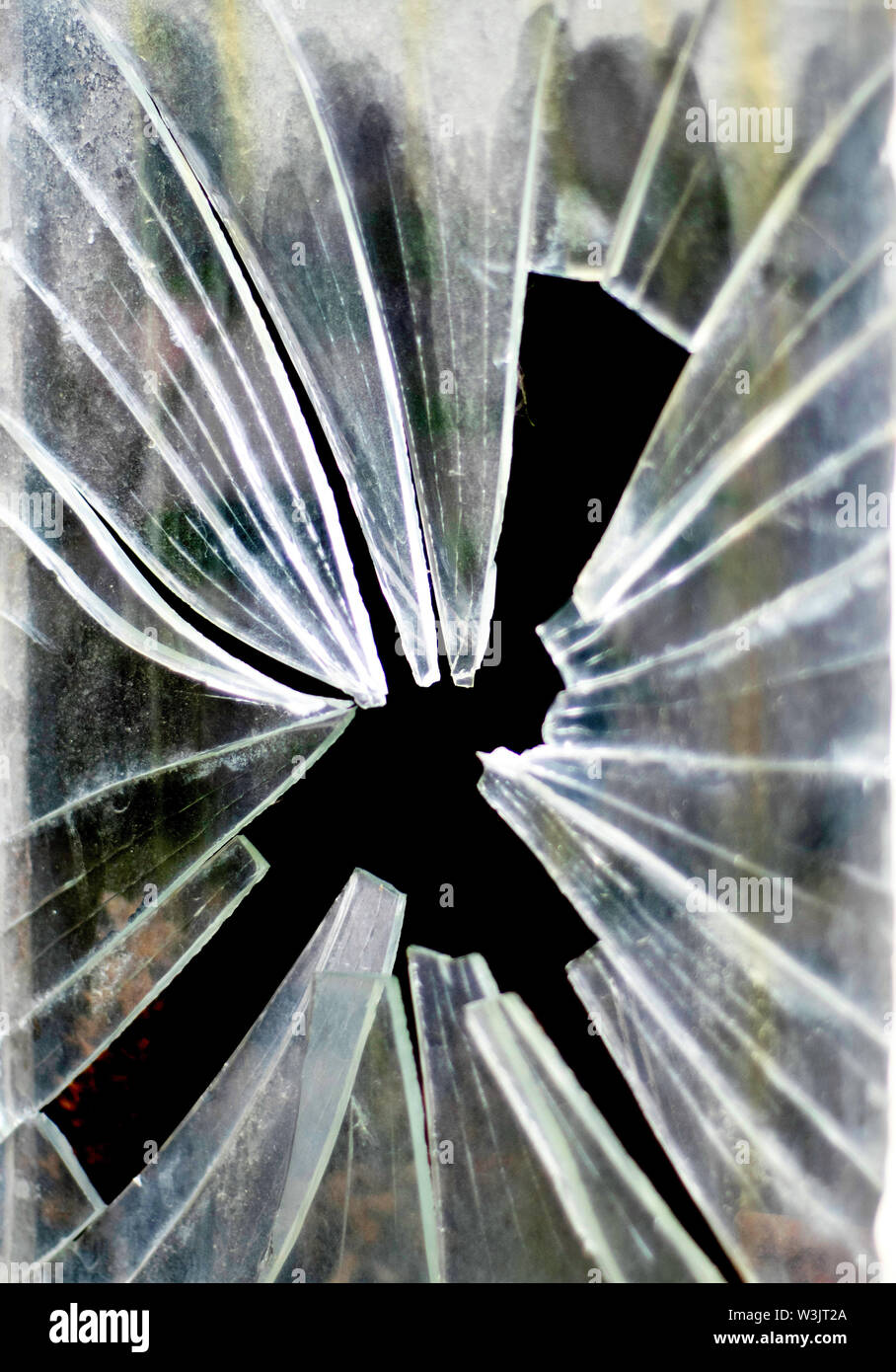 Sharp shards of broken glass from a smashed window pane - Stock Image