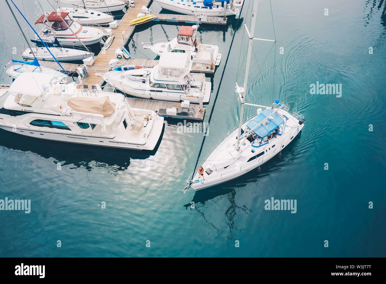 A white boat leaving the marina docks sailing on the water - Stock Image