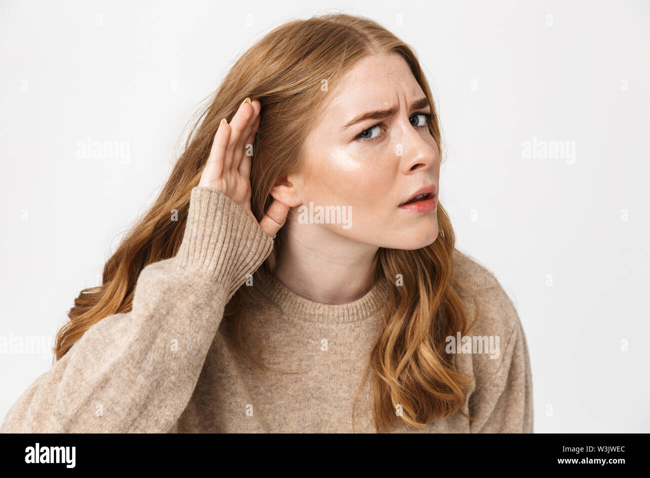 Attractive young girl wearing sweater standing isolated over white background, trying to hear rumors - Stock Image