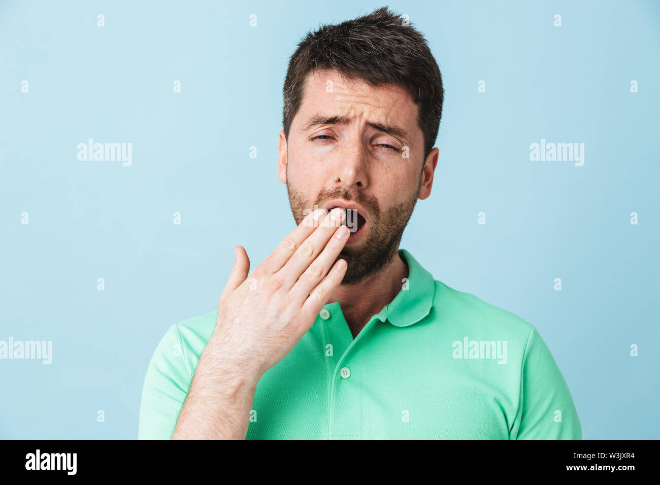 Image of a tired young handsome bearded man posing isolated over blue wall background yawning. - Stock Image