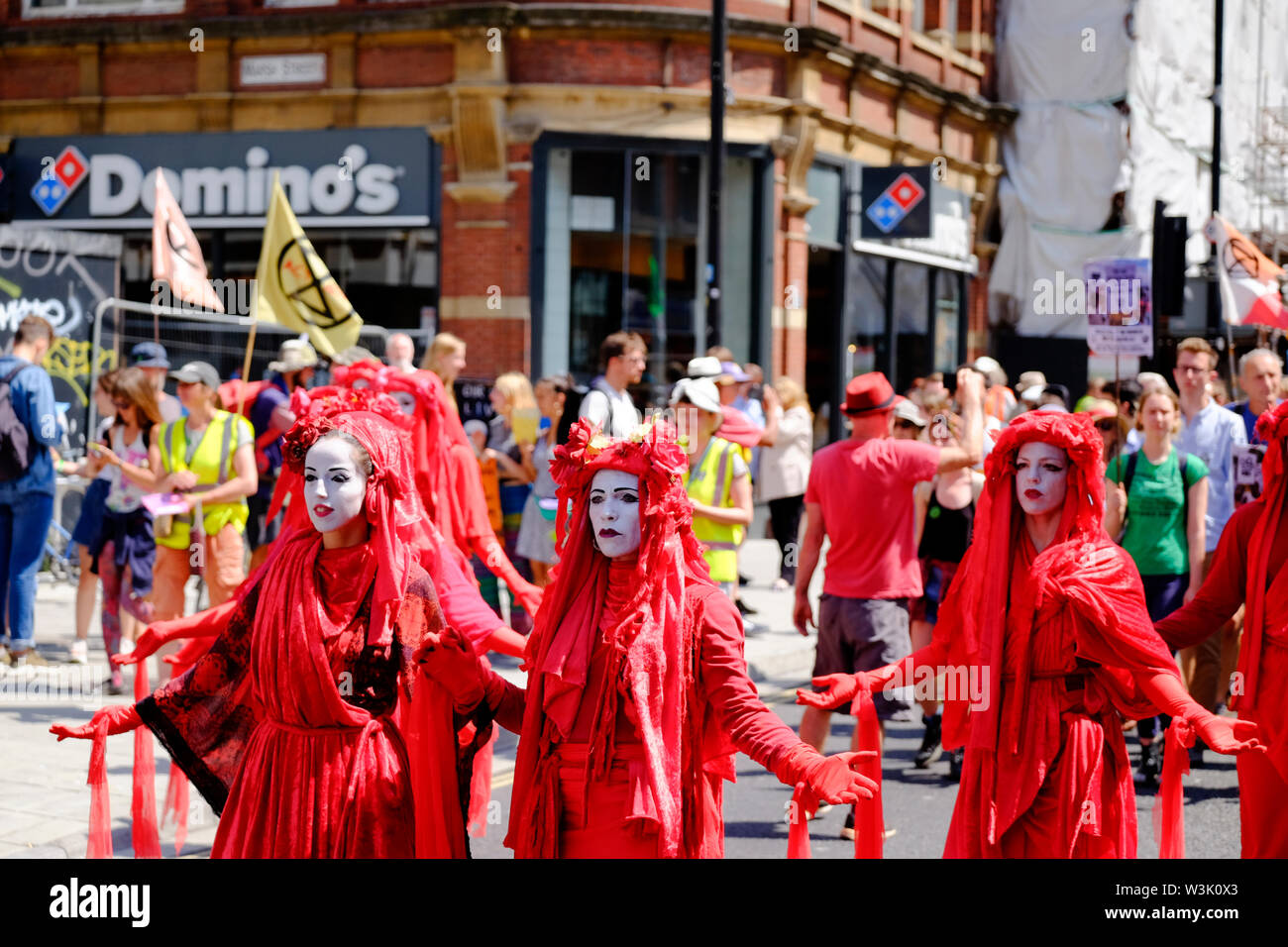 Bristol, UK, 16th July 2019.  Red Brigade at Day 2 of the Extinction rebellion movement summer uprising, the occupation of Bristol Bridge continues. The protest is to raise awareness of the speed of climate change and the lack of action to stop it. The protestors have worked with local agencies to ensure a safe and peaceful protest, police are present and diversions in place. Further occupations are planned throughout the city this week. Marching to college green. Credit: Mr Standfast / Alamy Live News Stock Photo