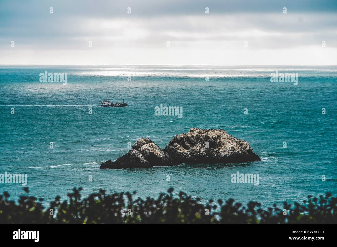 A Big rocks in the middle of the sea and a coast guard sailing in the distance - Stock Image