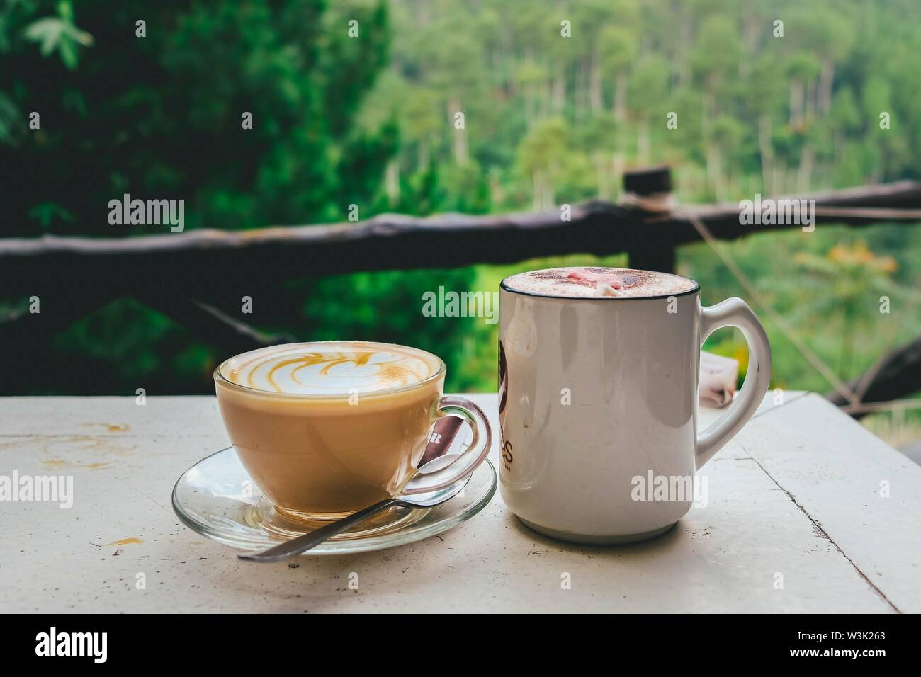 A closeup of a delicious latte and hot chocolate in cups on a table in the balcony - Stock Image
