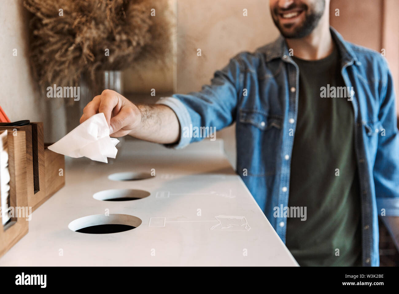 Image of caucasian cheerful man wearing denim shirt smiling and throwing paper garbage to separate collection bins for recycling in cafe indoors - Stock Image
