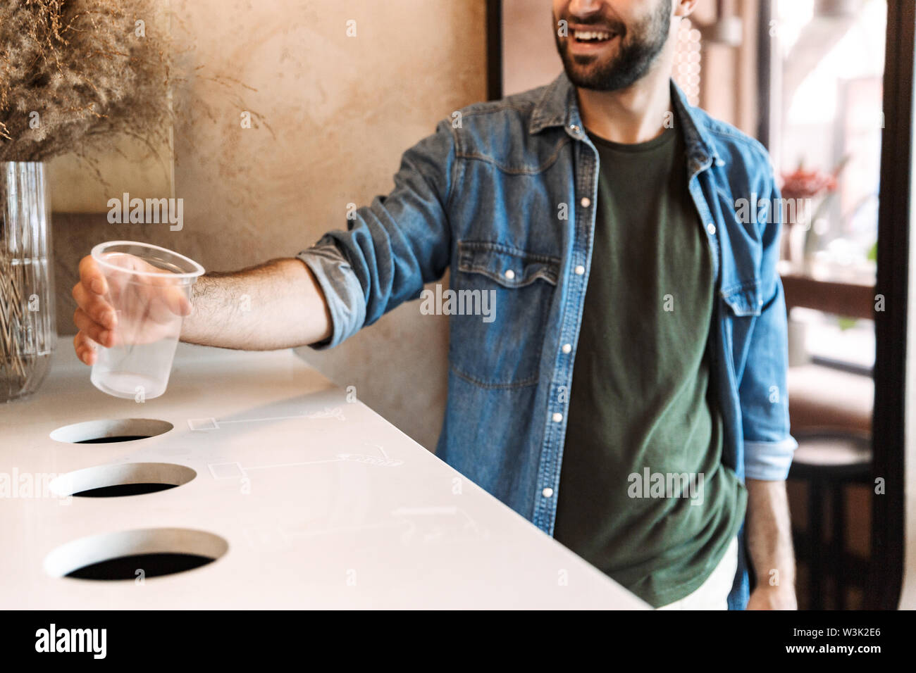Image of masculine young man wearing denim shirt smiling and throwing plastic garbage to separate collection bins for recycling in cafe indoors - Stock Image