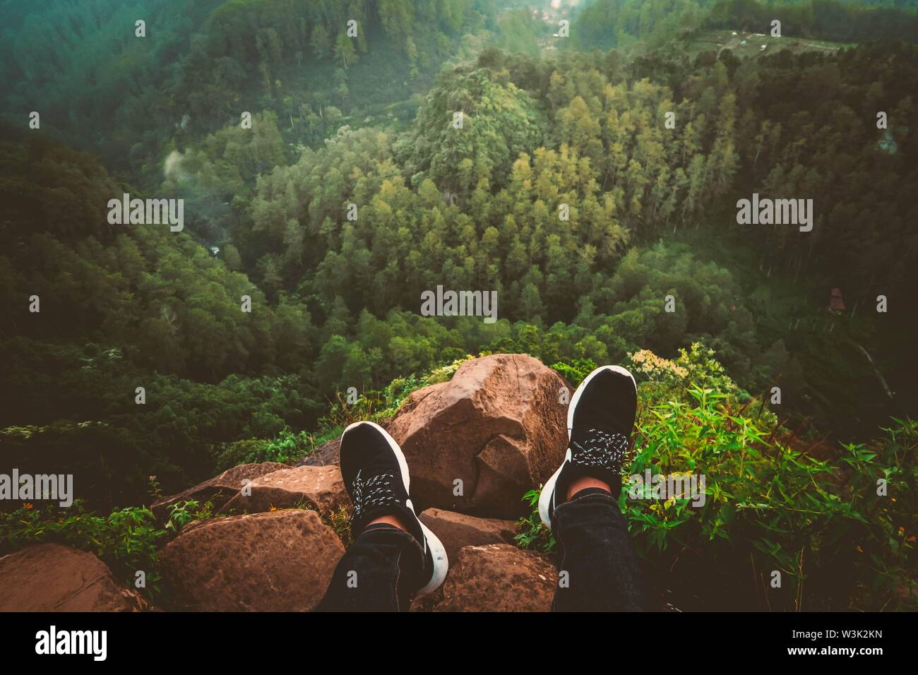 A person's feet in sneakers sitting on a rocky cliff edge looking at a beautiful forest and hills - Stock Image