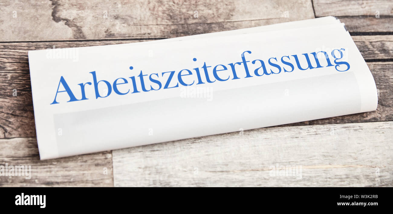 Arbeitszeiterfassung (German for: working time tracking) as a headline of a newspaper on a desk - Stock Image