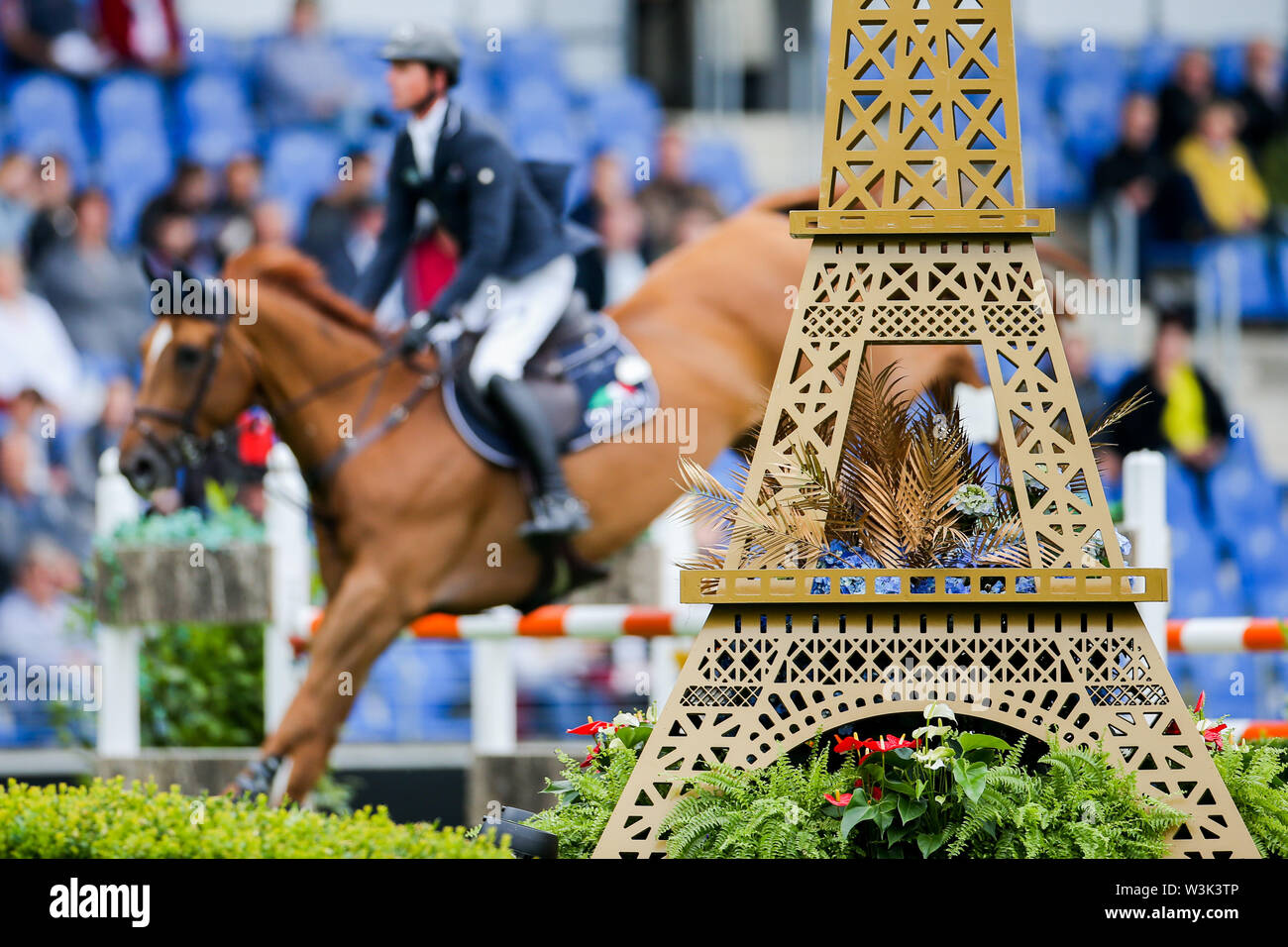 Aachen, Germany. 16th July, 2019. CHIO, equestrian sports, jumping: A rider jumps over an obstacle behind the model of an Eiffel Tower. France is this year's partner country of the tournament. Credit: Rolf Vennenbernd/dpa/Alamy Live News - Stock Image