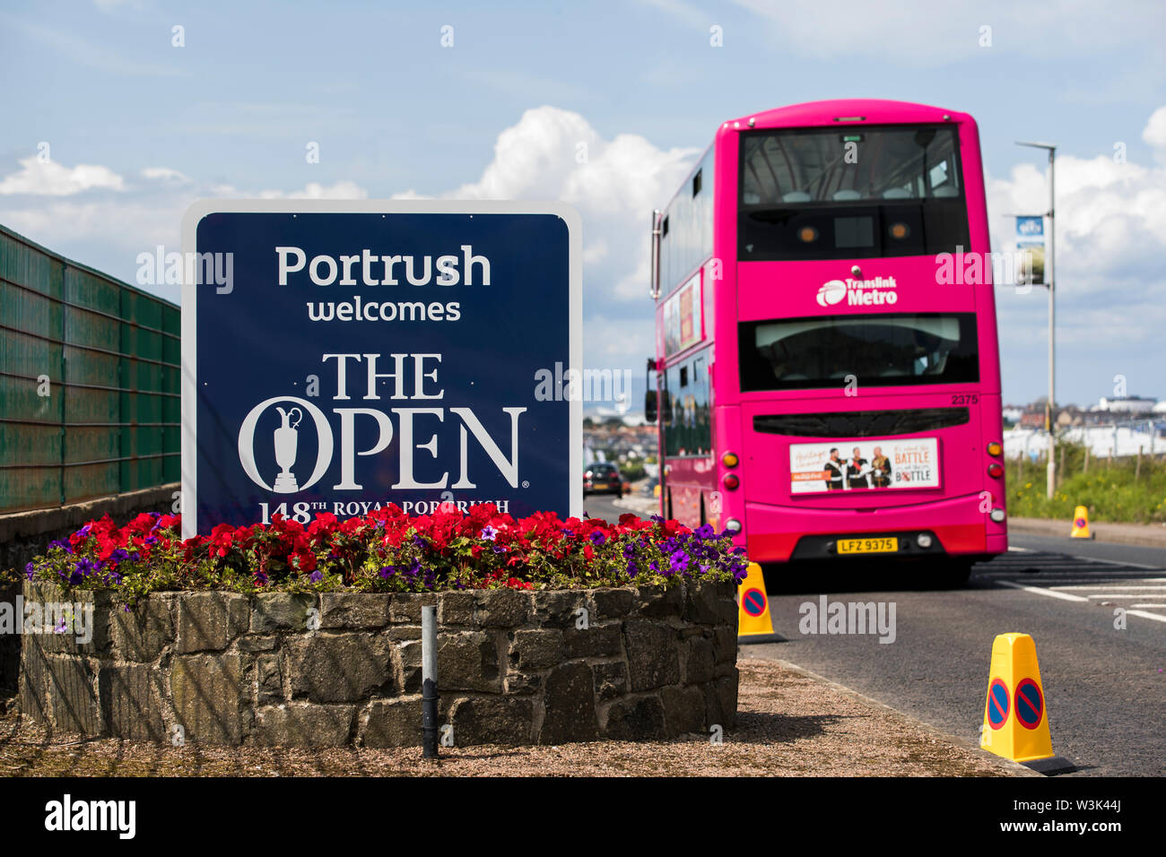 A Translink Metro bus from Belfast drives past a sign welcoming visitors to Portrush during preview day three of the Open Championship 2019 at Royal Portrush Golf Club. - Stock Image